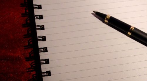 a biro lying across a pad of lined paper